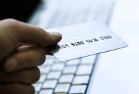 Kreditkarte die durch eine Hand über einem Computer gehalten wird