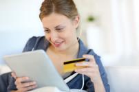 Eine Frau beim Einkaufen im Internet mit ihrer Kreditkarte