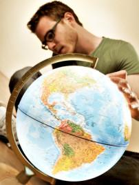 Person die auf einem Globus seine Reise plant