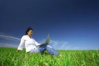 Frau mit Laptop auf einer Wiese